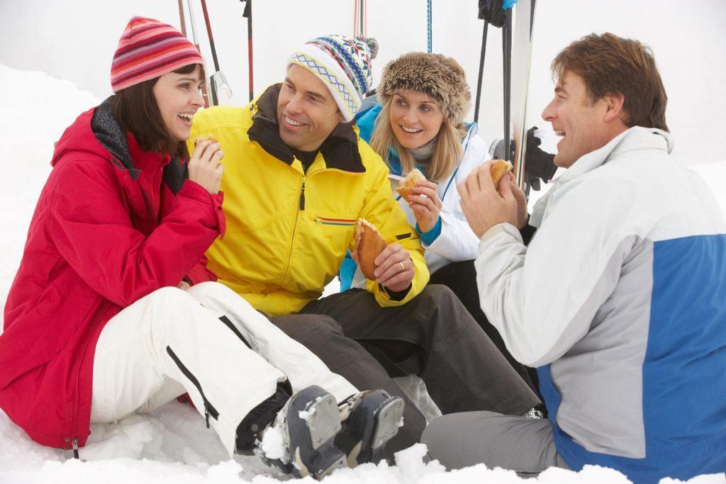 Amigos en su viaje de esquí comiendo fuera pistas